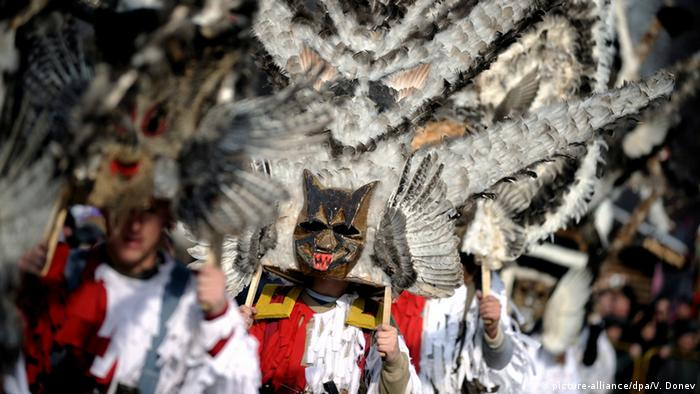 Man dressed in costumes with feathered masks