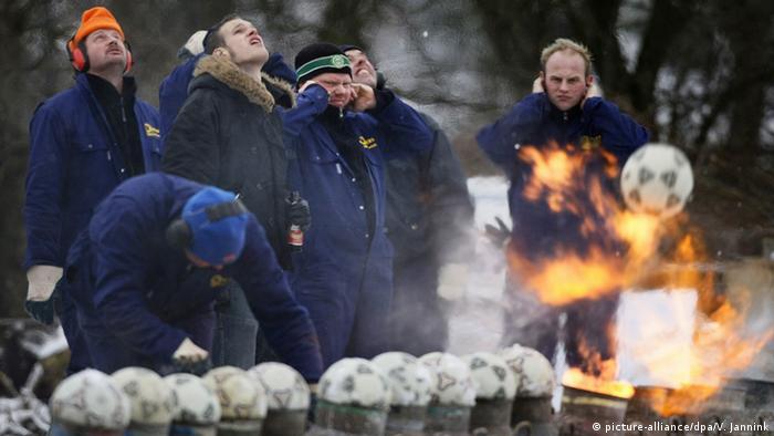 Mehrere Männer schießen mit Milchkannen. Foto: dpa