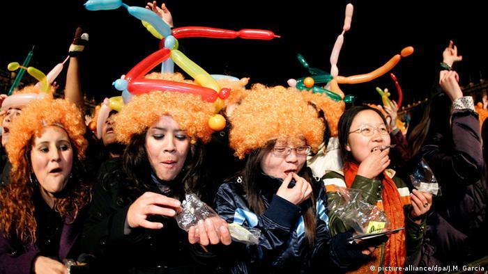 Junge Frauen essen zu Mitternacht Trauben. Foto: dpa