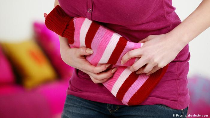 woman holding a hot water bottle to her stomach