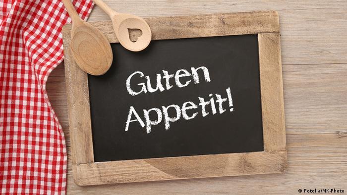 Kleine Tafel mit Holzrahmen und der Kreide-Aufschrift Guten Appetit!, umrahmt von zwei Holzlöffel, einer davon mit eingefrästen Herzem, und einer rot-weiß karierten Tischdecke (Foto: Fotolia/MK-Photo).