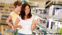 Frau kauft Shampoo im Drogeriemarkt