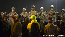 National Guard soldiers stand watch over the Ferguson Police Department as protesters chant in front of them during a third night of protests in Ferguson, Missouri November 26, 2014. National Guard troops and police aimed to head off a third night of violence on Wednesday in Ferguson, Missouri, as more than 400 people have been arrested in the St. Louis suburb and around the United States in civil unrest after a white policeman was cleared in the killing of the unarmed black teenager. REUTERS/Lucas Jackson (UNITED STATES - Tags: CIVIL UNREST CRIME LAW)