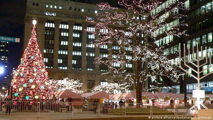 Árvore de Natal iluminada em uma praça com barraquinhas.