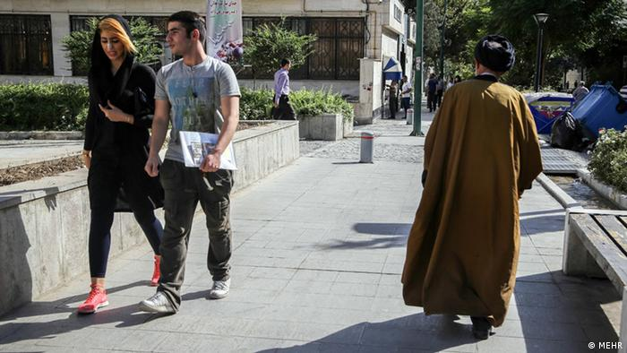 Two trendy young Iranians walk alongside a Mullah dressed in brown.
