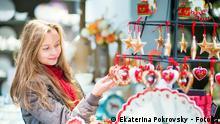 Young girl selecting Christmas decorations at Parisian Christmas market. Copyright: Ekaterina Pokrovsky - Fotolia #72125155