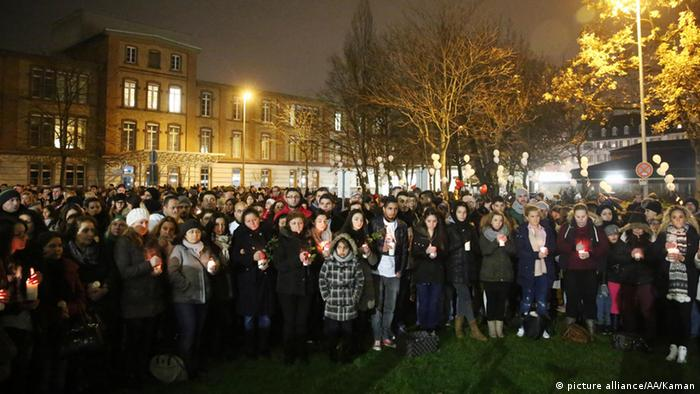Hundreds of vigilers stand outside in the evening.