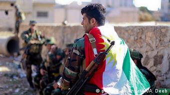 man with flag draped around his shoulders copyright: Ahmed Deeb - Anadolu Agency