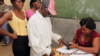 Ein Mann tunkt seinen Finger in Tinte vor der Wahlurne Foto: Dirk Heinrich (AP)