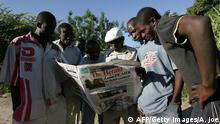 A group of Zimbabweans read a local newspaper