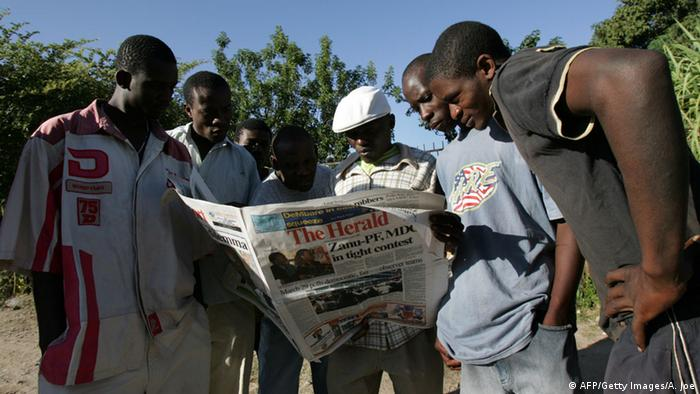 A group of young people on the street in Harare, Zimbabwe reading a newspaper