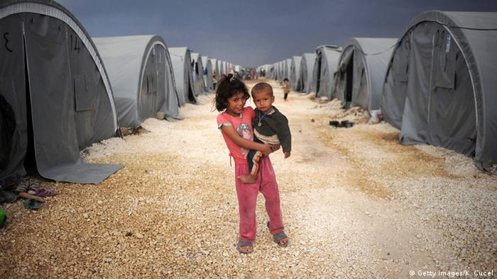 A Syrian refugee girl carries a toddler in a camp in Turkey.