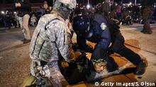 FERGUSON, MO - NOVEMBER 28: Police and national guard arrest a demonstrator outside the police station November 28, 2014 in Ferguson, Missouri. The Ferguson area has been struggling to return to normal since the August 9 shooting of Michael Brown, an 18-year-old black man, who was killed by Darren Wilson, a white Ferguson police officer. Monday, when the grand jury announced that Wilson would not face charges in the shooting, rioting and looting broke out throughout the area leaving several businesses burned to the ground. (Photo by Scott Olson/Getty Images)