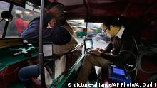 In this Tuesday, Nov. 25, 2014 photo, U.S. scientist Joshua Apte, right, monitors pollution levels on his laptop as he travels in an open-aired auto-rickshaw during rush-hour traffic in New Delhi, India. Apte has alarming findings for anyone who spends time on or near the roads in this city of 25 million, with numbers far worse than the ones that have already led the World Health Organization to rank New Delhi as the world¿s most polluted city. Average pollution levels, depending on the pollutant, were 50 percent to 8 times higher on the road than urban background readings, including official ambient air pollution measures, according to research by Apte and his partners at the University of California, Berkeley, and the Indian Institute of Technology in New Delhi. (AP Photo/Altaf Qadri)