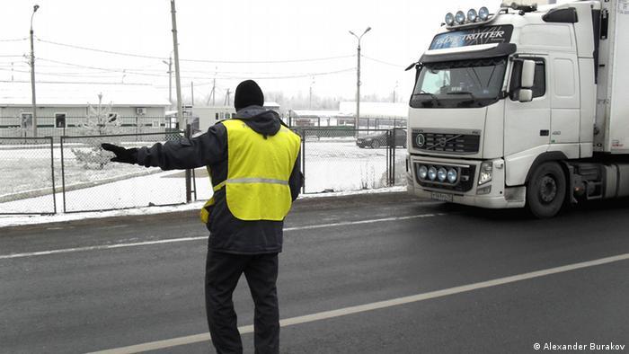 Сотрудник таможни указывает водителю машины, куда ему следует ехать