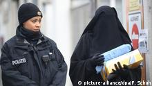 Eine verschleierte Frau kommt am 13.01.2013 in Berlin zu einem Treffen der Salafisten und geht an einer Polizistin vorbei. Nachdem den Salafisten Räumlichkeiten für ein bundesweites Treffen in Kreuzberg gekündigt wurden, haben sie sich in einem Veranstaltungzentrum in Neukölln getroffen. Bei der Veranstaltung sollen mehrere führende Salafisten sprechen. Foto: Florian Schuh/dpa