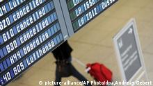 A woman walks near a panel listing cancelled flights at the airport in Munich, Germany, Monday Dec. 1, 2014. German airline Lufthansa says it has canceled about half of its flights after pilots went on strike in an ongoing dispute over retirement benefits. The airline, Germany's largest, said Monday that 1,350 of its 2,800 flights scheduled through the strike's end Tuesday at midnight have been cancelled, affecting 150,000 passengers. The strike was primarily focused on Lufthansa's inner-Europe flights on Monday but was to be extended to long-haul flights Tuesday. (AP Photo/dpa,Andreas Gebert)