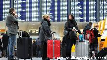 Flugreisende stehen am 01.12.2014 vor einer Anzeigetafel am Flughafen in München (Bayern). Nach Mitteilung der Pilotengewerkschaft Vereinigung Cockpit (VC) soll am Montag von 12 Uhr bis Dienstag 23.59 Uhr deutschlandweit gestreikt werden. Foto: Andreas Gebert/dpa