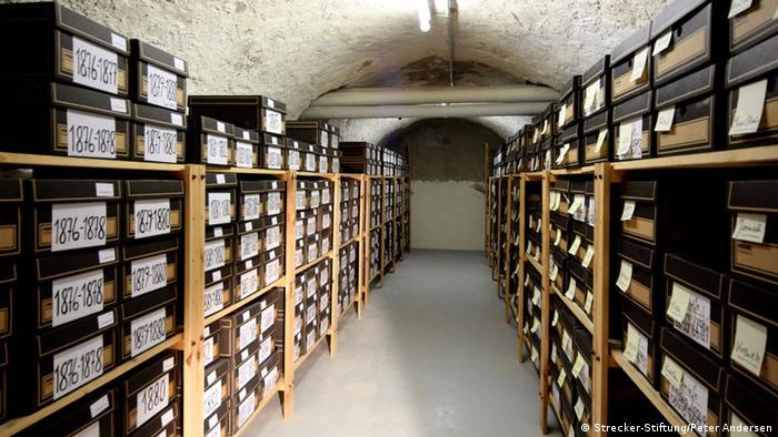 Blick in das Archiv des Schottverlags. In Regalen lagern beschriftete Dokumentenkisten