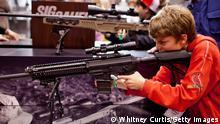 Symbolbild - USA Waffenlobby NRA Halbautomatisches Gewehr Messe Kind