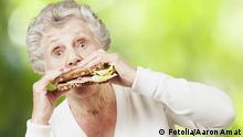 Ältere Frau beißt in Sandwich