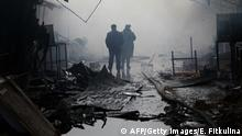 Bildunterschrift:People walk past burnt out kiosks at a street market close to a destroyed building housing the housing the local media known as the Press House, in central Grozny, on December 4, 2014. Heavily-armed gunmen attacked a police post killing several officers before storming a building housing the local media and a school in the capital. AFP PHOTO/ELENA FITKULINA (Photo credit should read ELENA FITKULINA/AFP/Getty Images)