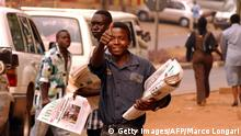 A newspaper seller gives a thumbs-up 31 July 2002 in Kigali as newspaper sales increased, with the population eager to read of the peace agreement signed 30 July between the Democratic Republic of Congo and Rwanda. AFP PHOTO Marco Longari (Photo credit should read MARCO LONGARI/AFP/Getty Images)