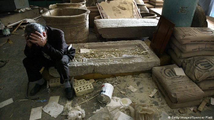 A man sits with his head in his hands amid ancient objects, Copyright: Mario Tama/Getty Images
