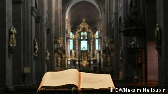 An open Bible backed by the inside of the Cathedral of St. Peter in Worms, Germany.