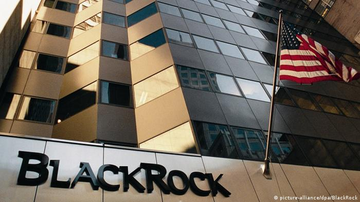 A picture of the the BlackRock headquarters building in New York, with an American flag flying in front of the huge glass facade
