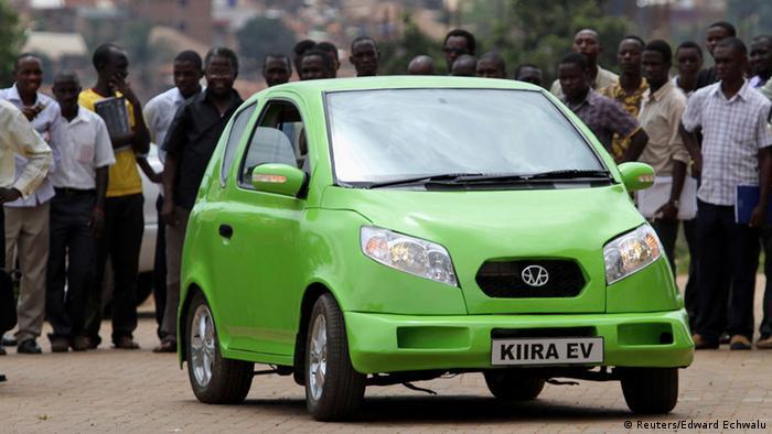 People surround a green Kiira electric car