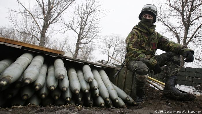 A soldier stands next to weapons in east Ukraine
