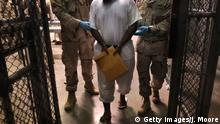 GUANTANAMO BAY, CUBA - MARCH 30: (EDITORS NOTE: Image has been reviewed by the U.S. Military prior to transmission.) U.S. Navy guards escort a detainee after a 'life skills' class held for prisoners at Camp 6 in the Guantanamo Bay detention center on March 30, 2010 in Guantanamo Bay, Cuba. U.S. President Barack Obama pledged to close the facility by early 2010 but has struggled to transfer, try or release the remaining detainees from the facility, located on the U.S. Naval Base at Guantanamo Bay, Cuba. (Photo by John Moore/Getty Images)
