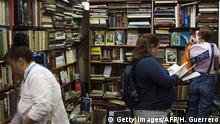 Visitors look at books during the International Book Fair in Guadalajara, Mexico, on November 30, 2014. Argentina is this year's guest country of honour of the fair. AFP PHOTO/Hector Guerrero (Photo credit should read HECTOR GUERRERO/AFP/Getty Images)