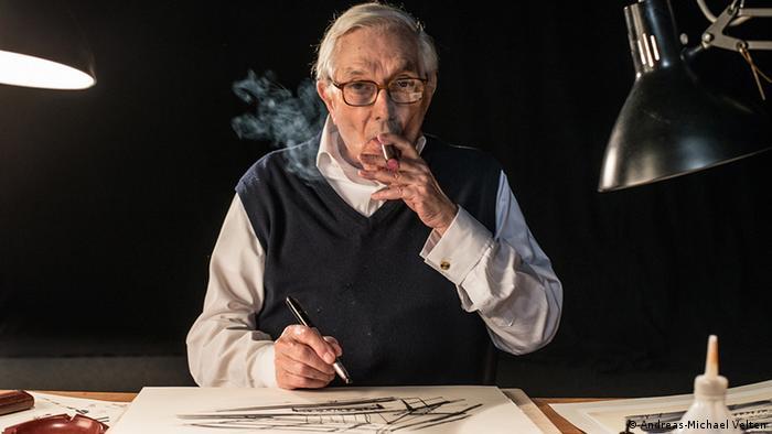 Ken Adam ist auf einem Foto zu sehen: Zigarre rauchend, den legendären Flo-Master-Filzstift gezückt, vor sich die Skizze einer Filmszene.