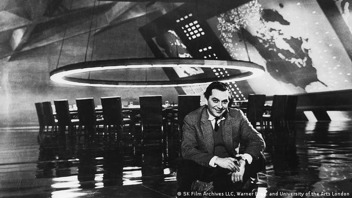 Schwarzweißfoto zeigt Ken Adam, der vor seinem Filmset War Room sitzt. Im Hintergrund ist der angeblich atomsichere Raum zu sehen, der aus einem großen runden Tisch mit Stühlen unter einer Lampe besteht.
