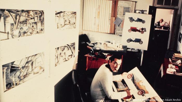 Ken Adams sitzt am Schreibtisch in seinem Studio mit Zigarre im Mund. Er trägt einen weißen Pullover und blickt in die Kamera.