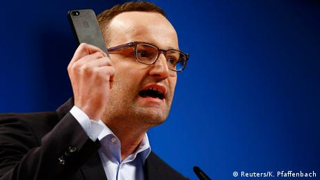 Jens Spahn holds a mobile phone in his hand as he speaks during the Christian Democratic Union (CDU) party convention