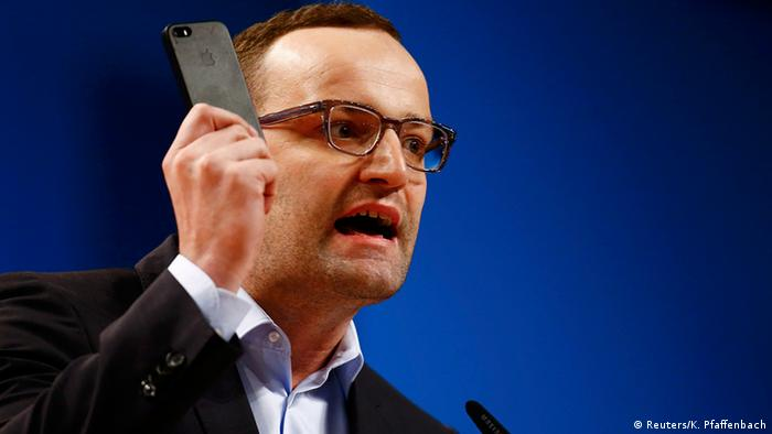 Jens Spahn holds a mobile phone in his hand as he speaks during the Christian Democratic Union party convention