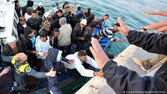 Ein Flüchtlingsboot wurde von der Marine gerettet und an Land gebracht. Während die Flüchtlinge an Land gehen wollen, machen Männer und Frauen mit ihren Händen eine abwehrende Geste. (Foto: picture-alliance/dpa/Ettore Ferrar)