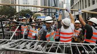 Workers remove a barricade at an area blocked by pro-democracy protesters near the government headquarters building at the financial Central district in Hong Kong December 11, 2014.
