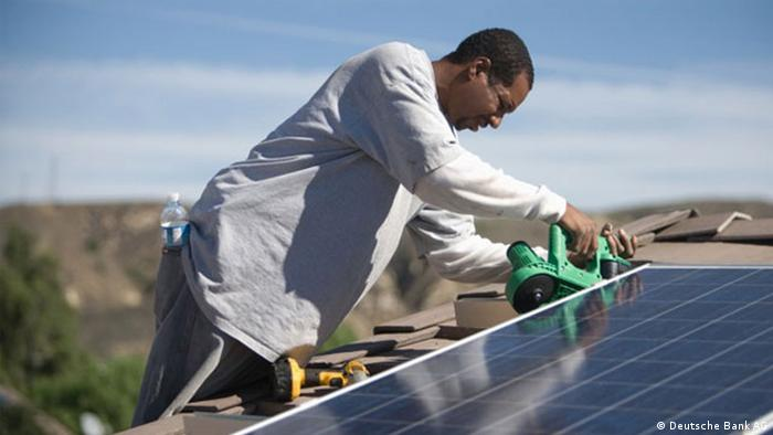 An African technician working on a solar panel.