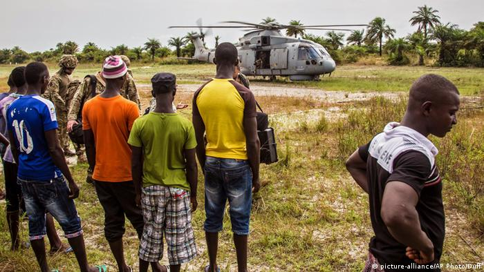 Local residents look at a British Navy helicopter after it made a food drop on Sherbro Island, Sierra Leone, Sunday, Dec. 7, 2014 (AP Photo/Michael Duff)