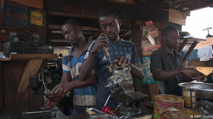 Three workers fix fuel pumps for trucks and buses. (Picture: Yepoka Yeebo, DW)