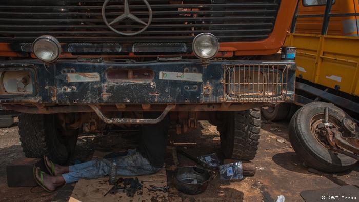 Ein Arbeiter sitzt unter dem Fahrerhaus eine Mercedes-LKW (Bild: Yepoka Yeebo, DW)