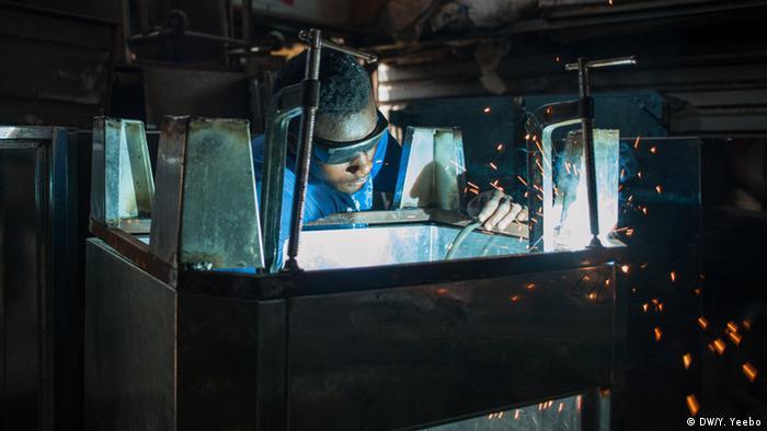 Ein junger Arbeiter schweißt Füße an einen Brotbackofen. (Bild: Yepoka Yeebo, DW)