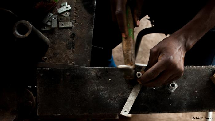 Detail of a worker's hand working with a hammer. (Picture: Yepoka Yeebo, DW)