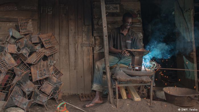 Ein Arbeiter schweißt einen Kohleofen zusammen. (Bild: Yepoka Yeebo, DW)