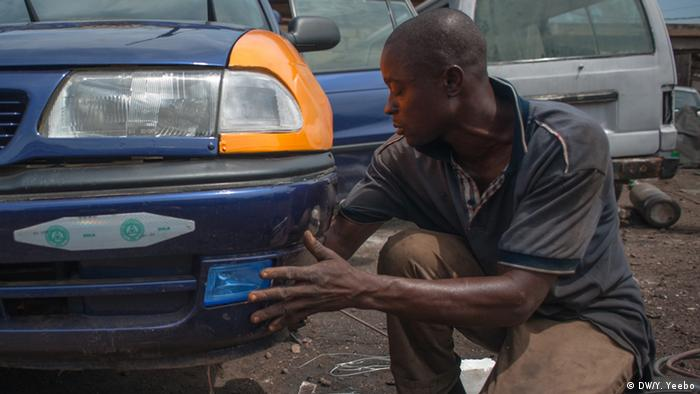 A mechanic fits the lights on an Opel taxi (Picture: Yepoka Yeebo, DW)
