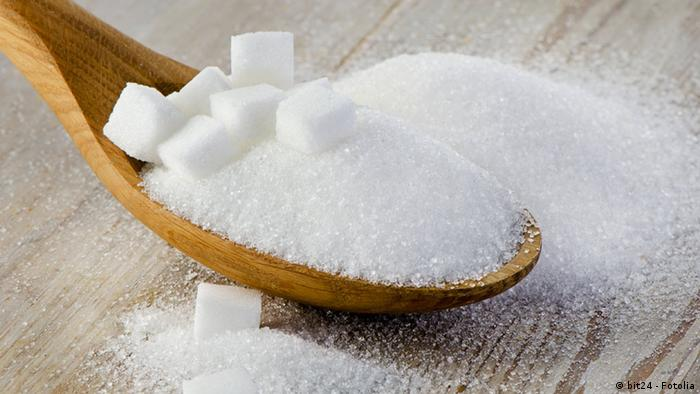 a spoon holding loose sugar and sugar cubes
